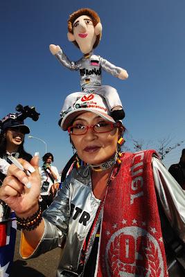 болельщица Михаэля Шумахера с куклой ка кепке на Гран-при Японии 2011