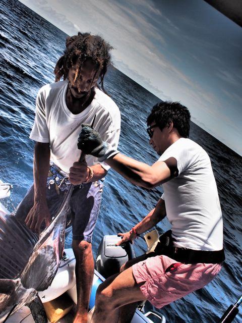Камуи Кобаяши держит рыбу-меч за острее