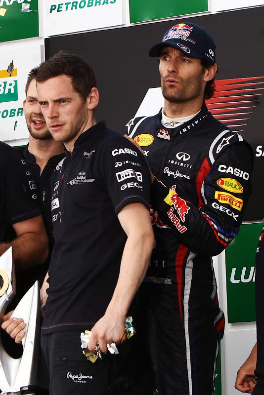 Марк Уэббер выглядывает из-за спины Ли Стивенсона на подиуме Интерлагоса на Гран-при Бразилии 2011
