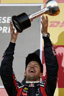 Себастьян Феттель подбрасывает свой трофей на подиуме Гран-при Японии 2011