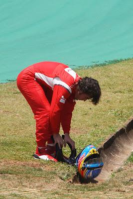 Фернандо Алонсо кладет шлем на землю после схода во во время первой сессии свободных заездов на Гран-при Бразилии 2011