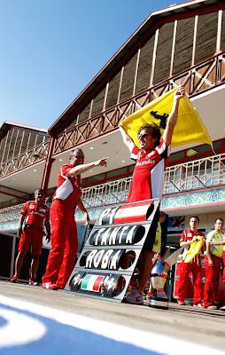 Стефано Доменикали показывает пальцем на Фернандо Алонсо с флагом Ferrari на Гран-при Европы 2012