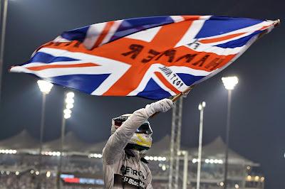 Льюис Хэмилтон c флагом празднует победу в чепионате и на Гран-при Абу-Даби 2014
