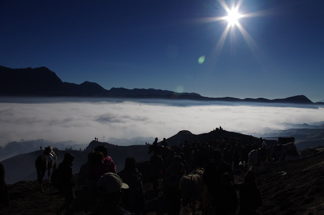 Breaking through the fog, a steady stream of pilgrims makes their way to the top of the volcano.