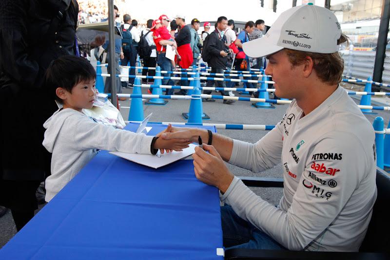 Нико Росберг жмет руку юному болельщику на автограф-сессии Гран-при Японии 2011