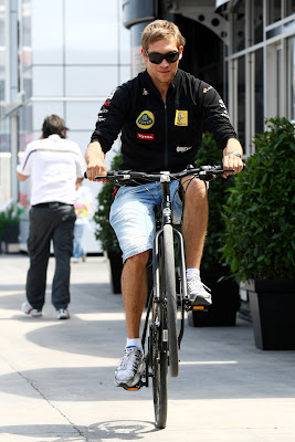 Виталий Петров едет на одном колесе на велосипеде по паддоку Валенсии на Гран-при Европы 2011