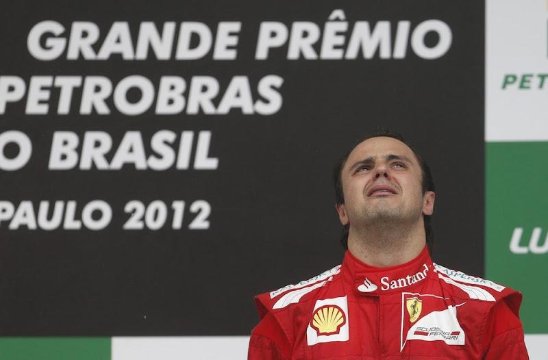 Фелипе Масса смотрит вверх на подиуме Интерлагоса на Гран-при Бразилии 2012