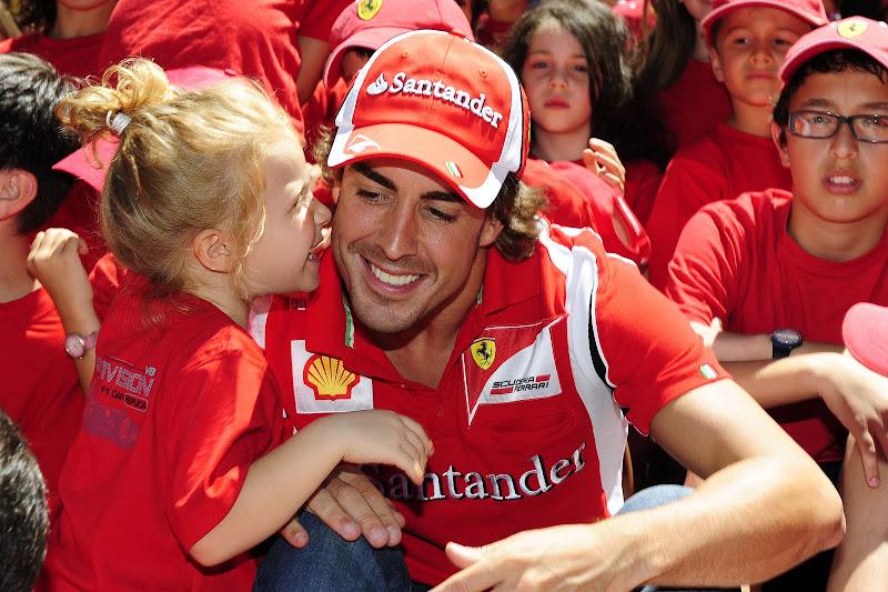 Фернандо Алонсо с маленькой девочкой на спонсорском мероприятии перед Гран-при Германии 2011