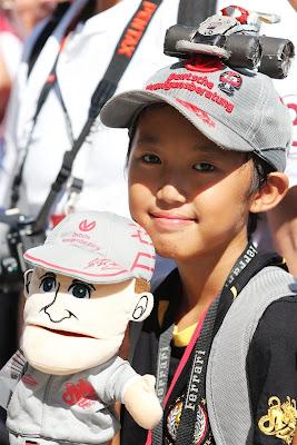 болельщица Михаэля Шумахера и Mercedes с куклой и мини-болидом на кепке на Гран-при Японии 2012