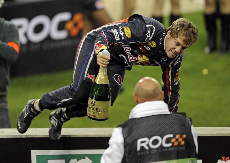 Себастьян Феттель перепрыгивает через ограждение с бутылкой шампанского на Гонке чемпионов 2011