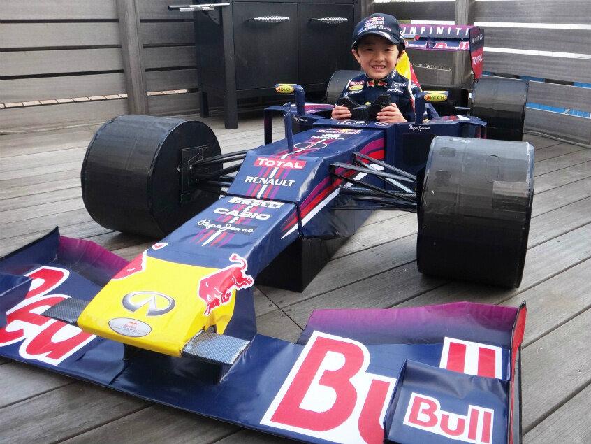 болид Red Bull RB9 из картона с юным болельщиком на борту