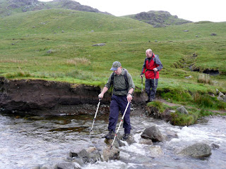 Negotiating a safe way across. We had to throw poles accros the beck to help a tricky crossing.