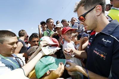 Себастьян Феттель раздает автографы на трибуне с болельщиками на Гран-при Венгрии 2013