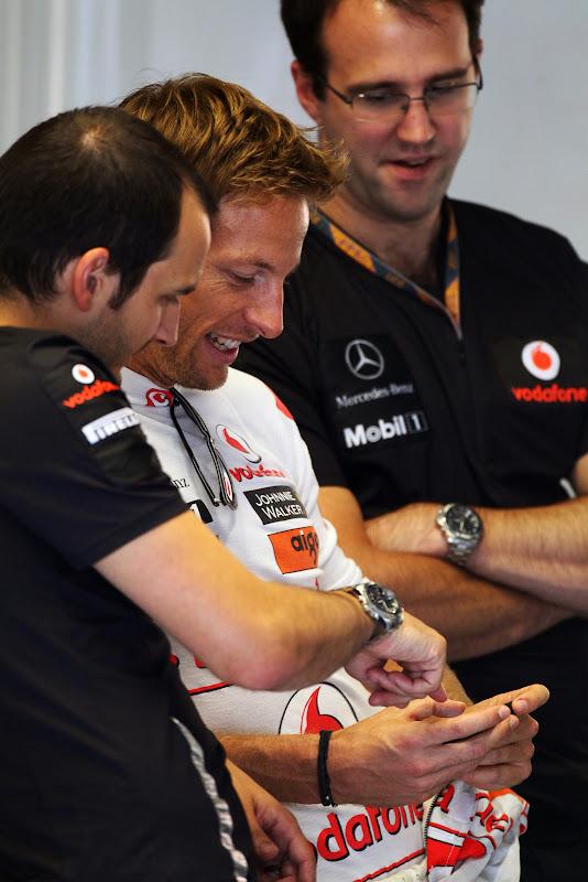 Дженсон Баттон показывает что-то забавное на телефоне механикам на Гран-при Италии 2011