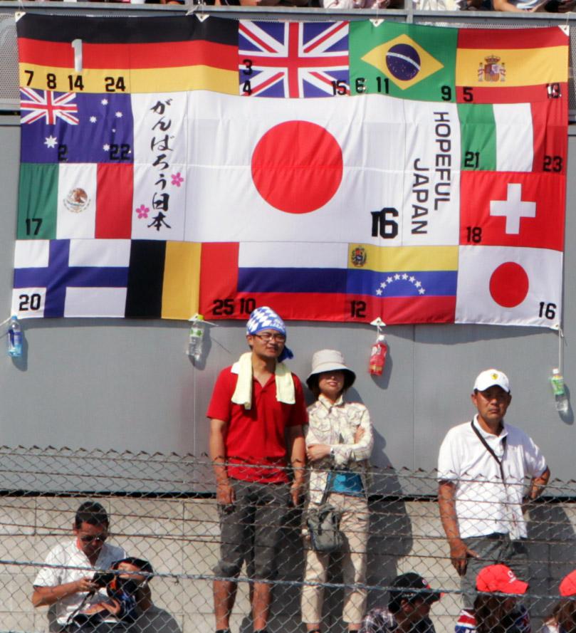 болельщики Камуи Кобаяши с флагами всех стран на трибунах Сузуки на Гран-при Японии 2011