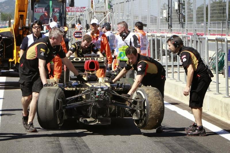 механики Lotus катят разбитый болид Кими Райкконена по пит-лейну на Гран-при Кореи 2013