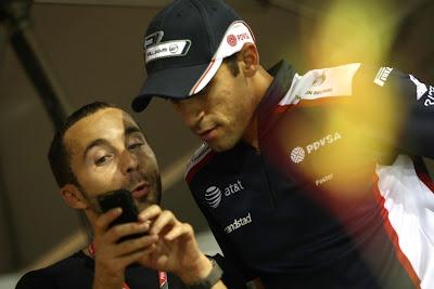 Пастору Мальдонадо показывают что-то на телефоне на Гран-при Сингапура 2011