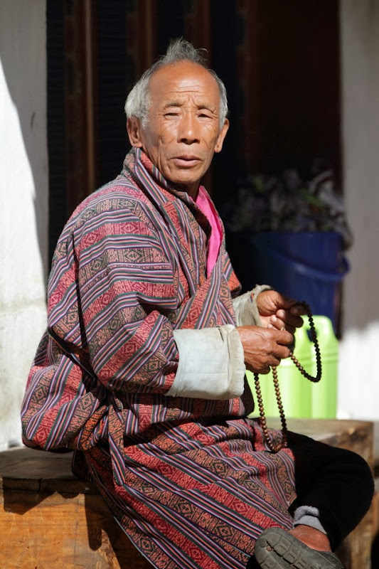 Old Bhutanese man in prayer at Trongsa, Bhutan