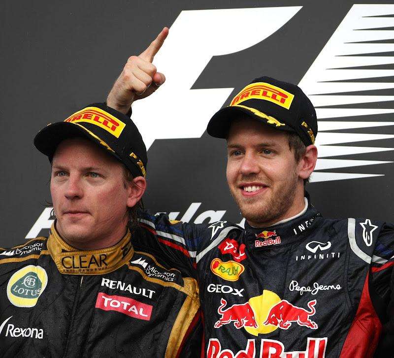 Себастьян Феттель показывает палец над головой Кими Райкконена на подиуме Гран-при Бахрейна 2012