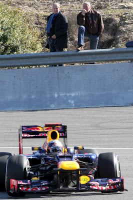 Хельмут Марко и Дитер Матешиц смотрят на проезжающий болид Red Bull Себастьяна Феттеля на предсезонных тестах 2012 в Хересе 9 февраля 2012