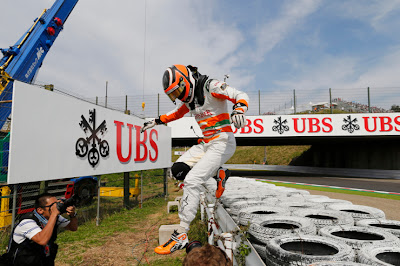 Нико Хюлькенберг спрыгивает с ограждения на трассе Сузука на Гран-при Японии 2012