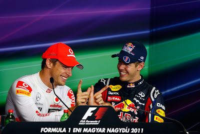 Дженсон Баттон показывает Себастьяну Феттелю что-то пальцами на пресс-конференции после гонги на Гран-при Венгрии 2011