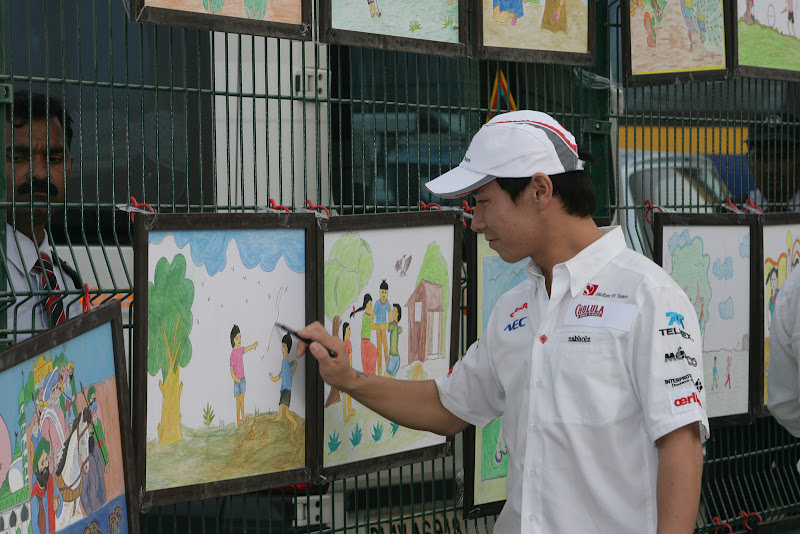Камуи Кобаяши ставит автограф на рисунках индийских школьников на Гран-при Индии 2011