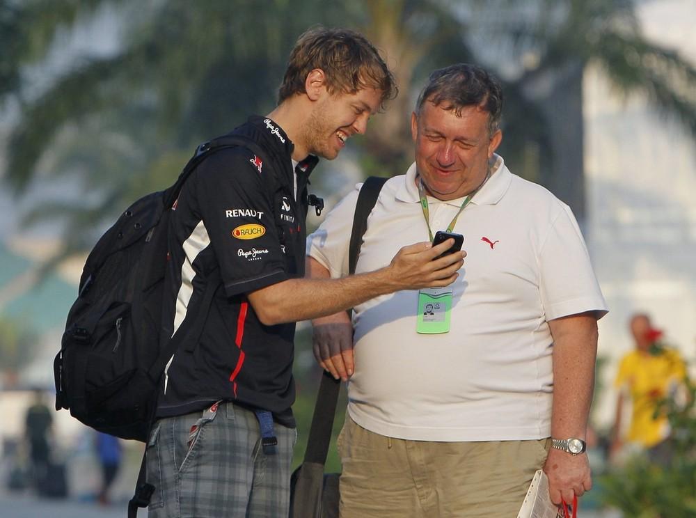 Себастьян Феттель показывает что-то на своем телефоне на Гран-при Малайзии 2012