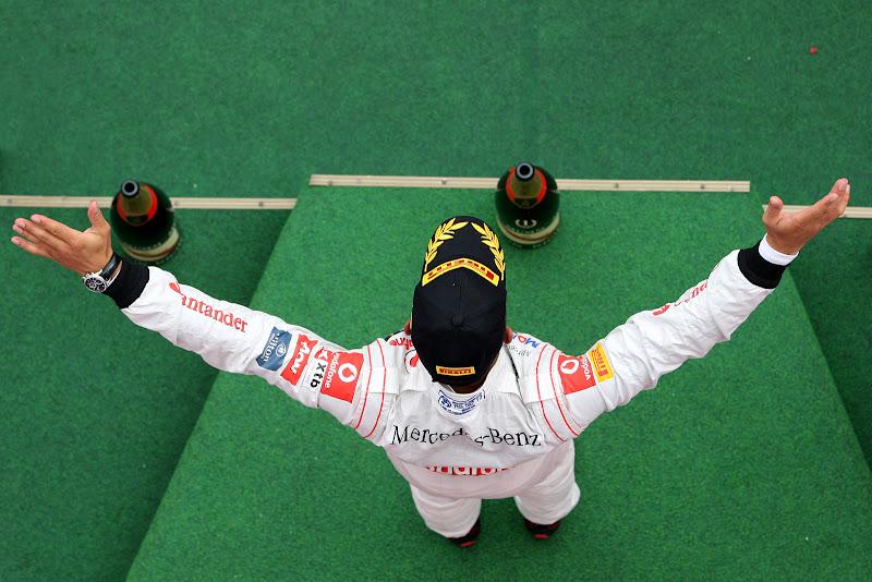 Льюис Хэмилтон празднует свою победу на подиуме Нюрбургринга на Гран-при Германии 2011