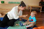 Our Montessori-trained toddler teachers engage your child one-on-one. Here, a young boy is enjoying a language lesson on the names of farm animals.