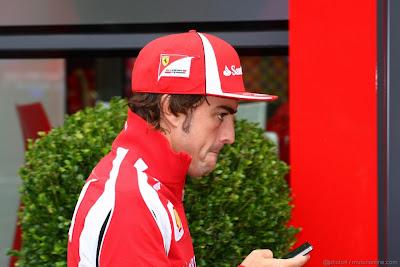 Фернандо Алонсо с телефоном проходит мимо зеленого куста у паддока Ferrari на Гран-при Венгрии 2011