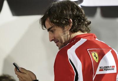 улыбающийся Фернандо Алонсо смотрит в телефон на Гран-при Сингапура 2011