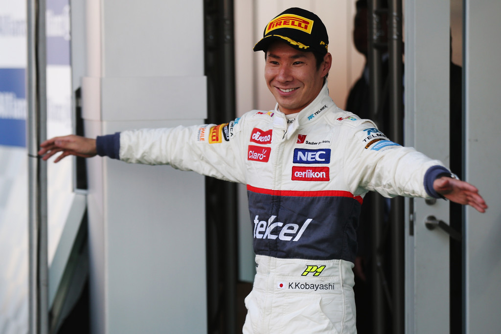 Камуи Кобаяши с распахнутыми объятиями на подиуме Сузуки на Гран-при Японии 2012