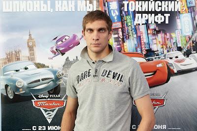 Виталий Петров на фоне постера Тачки 2