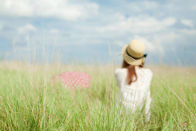 Ảnh cô gái đi trong vườn hoa cỏ may