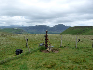 Burnbank Fell Summit with poles and rucksacks.