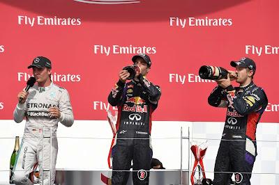 Нико Росберг дает интервью, а Даниэль Риккардо и Себастьян Феттель выпивают шампанское на подиуме Гран-при Канады 2014