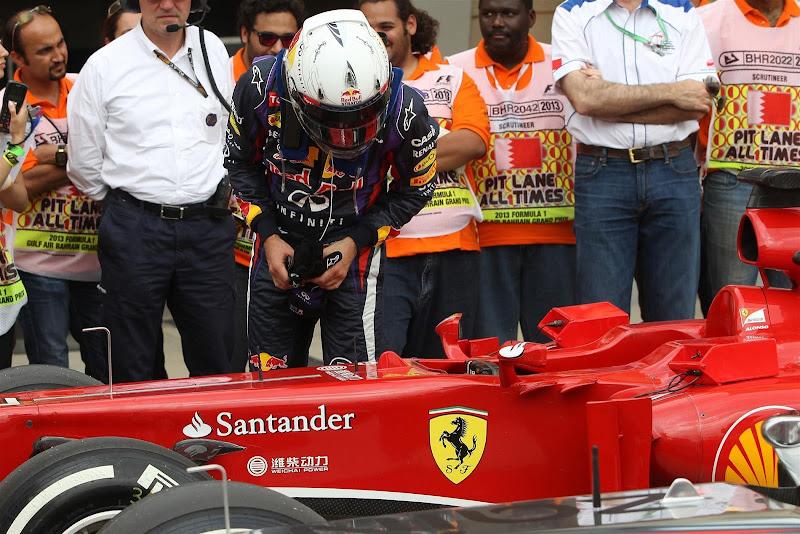 Себастьян Феттель разглядывает болид Ferrari после квалификации на Гран-при Бахрейна 2013