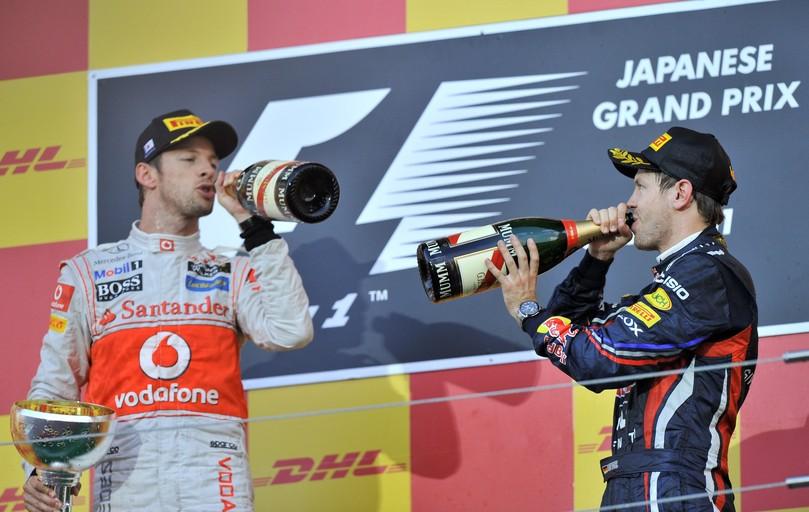 Дженсон Баттон и Себастьян Феттель пьют шампанское не подиуме Гран-при Японии 2011