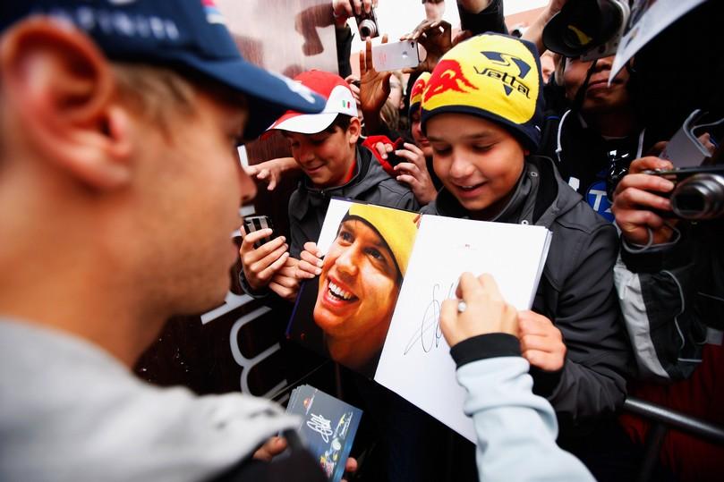 Себастьян Феттель на автограф-сессии Нюрбургринга дает автограф юному болельщику на Гран-при Германии 2011