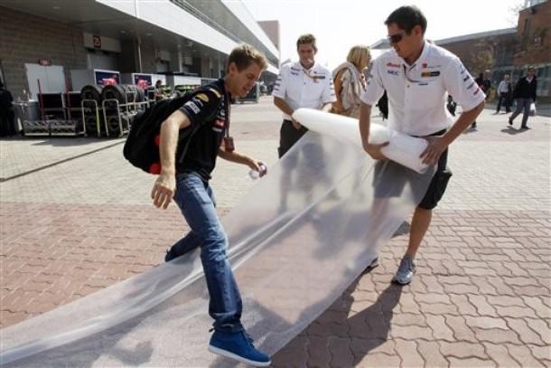 Себастьян Феттель перешагивает полиэтилен на Гран-при Кореи 2011