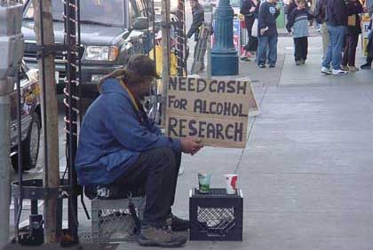 "Image of man holding cardboard sign ""Need Cash for Alcohol Research"""