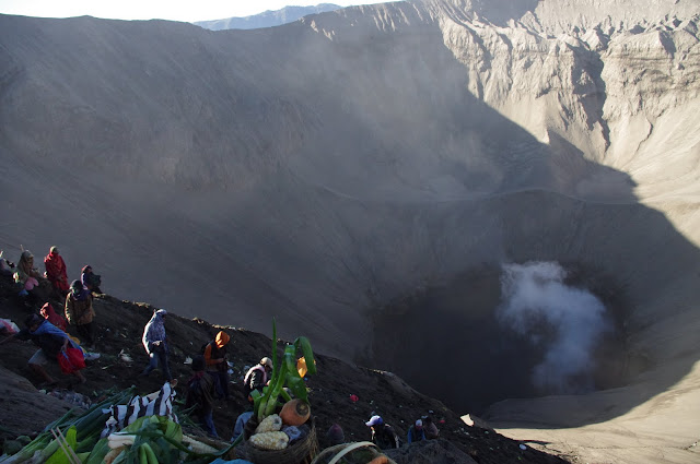 Locals climb into the volcano to collect offerings.