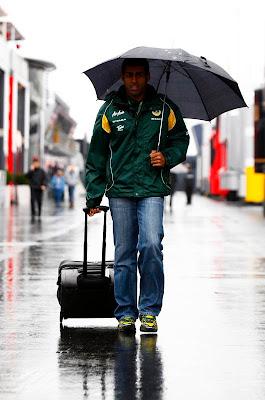 Карун Чандхок под зонтиком с чемоданом в паддоке Нюрбургринга на Гран-при Германии 2011