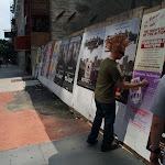Aden puts up Revolution stickers as we walk