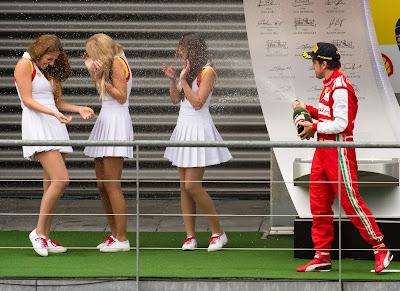 Фернандо Алонсо поливает шампанским девочек на подиуме Гран-при Бельгии 2013