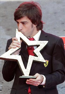 Фернандо Алонсо целует трофей в Мадриде 19 декабря 2011