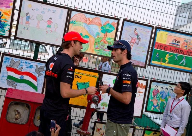 Дженсон Баттон и Марк Уэббер разговаривают на фоне рисунков на Гран-при Индии 2011