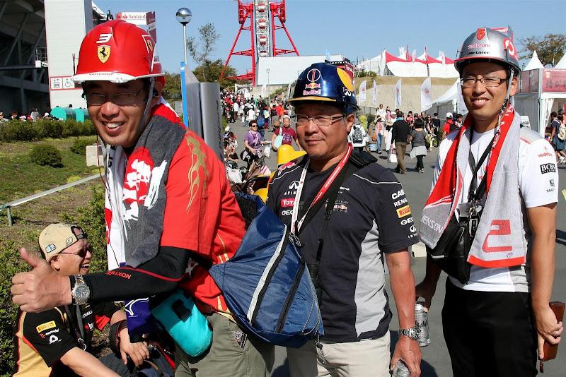 болельщики в оригинальных шлемах-болидах на Гран-при Японии 2013