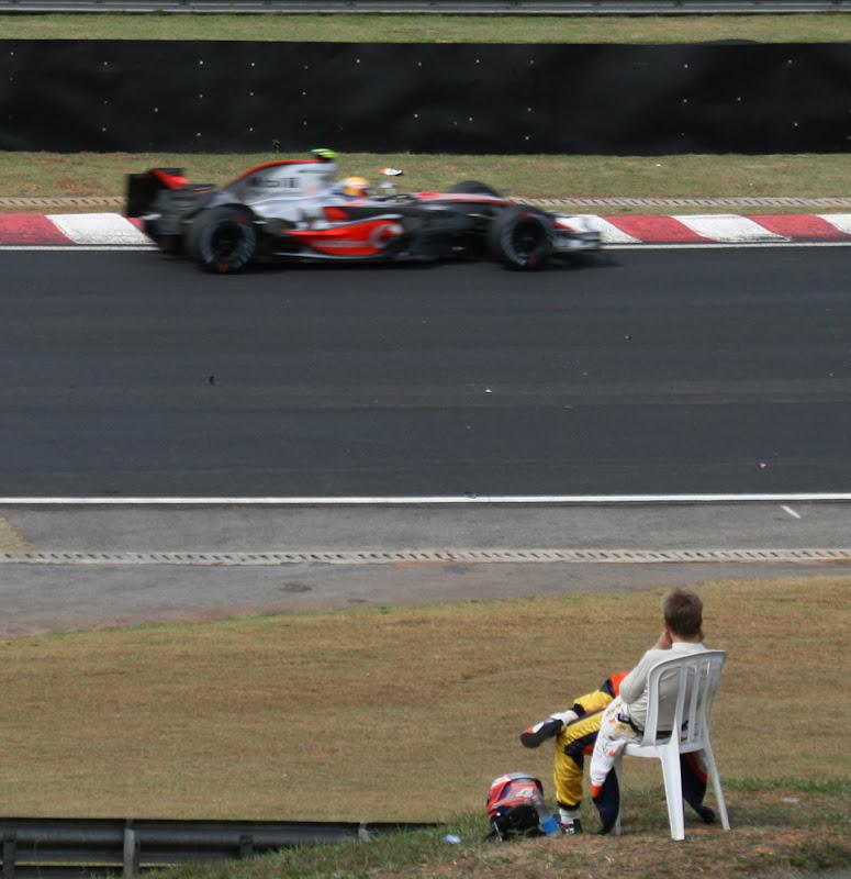 Хейкки Ковалайнен на пластиковом кресле смотрит на проезжающего Льюиса Хэмилтона на McLaren на Гран-при Бразилии 2007